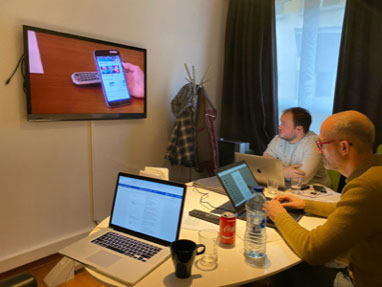 Image of a room of me and some colleagues watching a Walloon customer from Brussels interacting with the landingspage design.